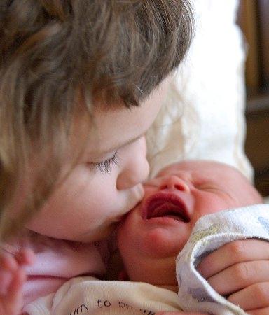 Chloe kissing her baby sister